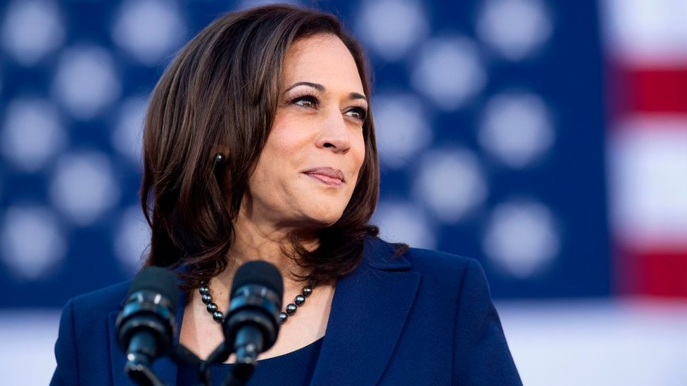 Kamala Harris standing in front of an American flag