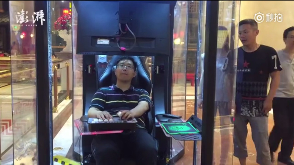 Man sitting in a pod, playing a computer arcade game at a shopping mall in China