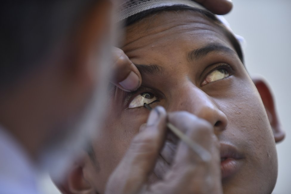 A herbal eye-liner is applied to the eyes of a Muslim