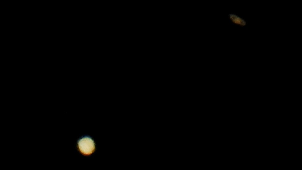 Jupiter (below) and Saturn (above) are pictured on the sky during the closest visible conjunction of them in 400 years, in La Linea de la Concepcion, southern Spain