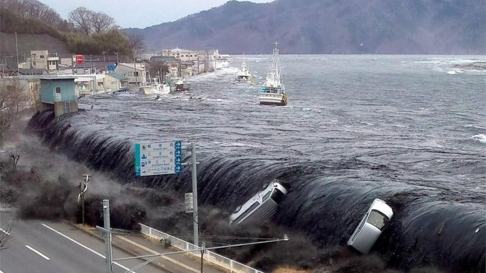 Tsunami breeching an embankment and flowing into the city of Miyako in 2011