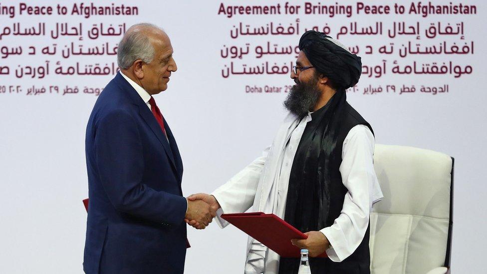 El representante especial de Estados Unidos para la reconciliación en Afganistán, Zalmay Khalilzad, da la mano al cofundador del Talibán, Mullah Abdul Ghani Baradar, durante la ceremonia de la firma del acuerdo en Qatar.