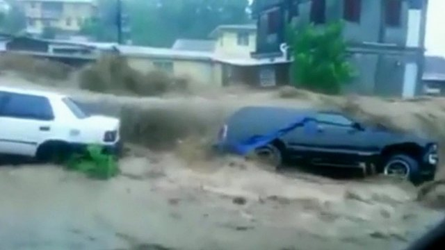 Floodwaters rush over cars