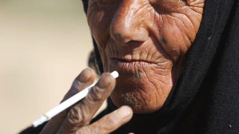 Žena puši cigaru