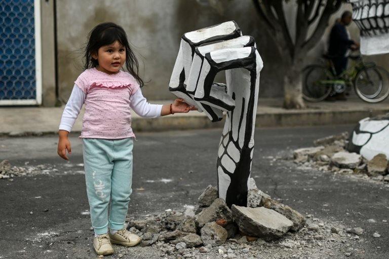 فتاة تلمس الهيكل العظمي المصنوع من الورق المقوى
