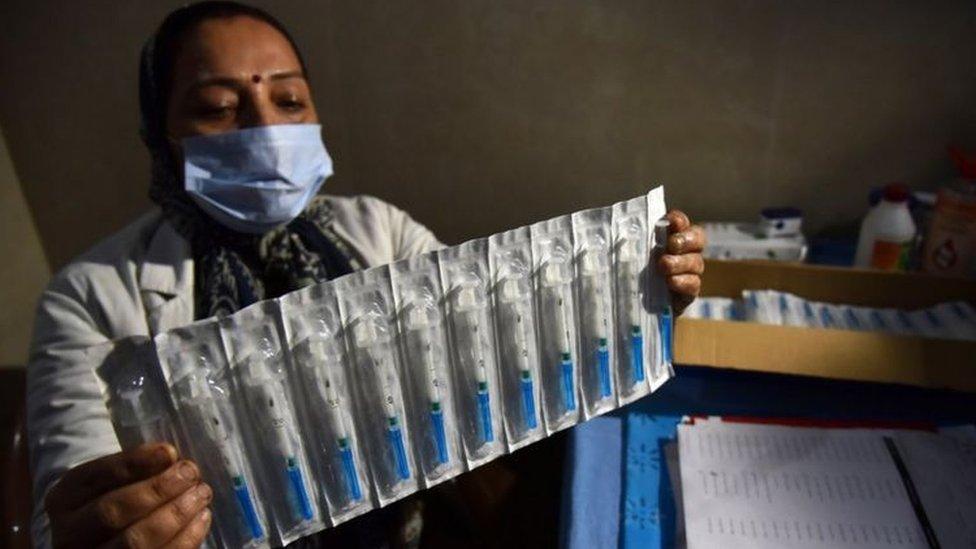 Enfermeira indiana segura as seringas que serão usadas na vacinação