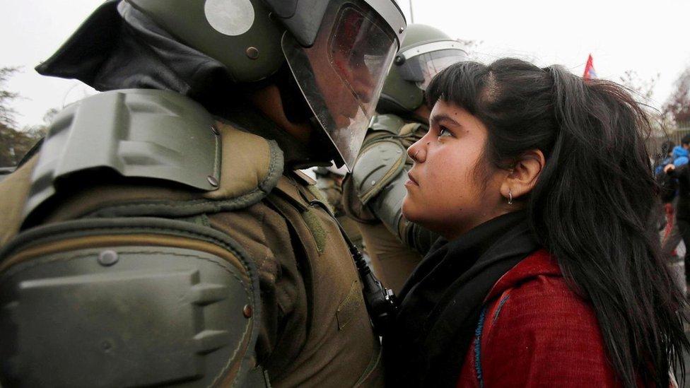 Una joven se enfrenta a un policía en una protesta