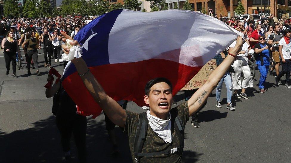 Joven con una bandera de Chile delante de cientos de manifestantes.