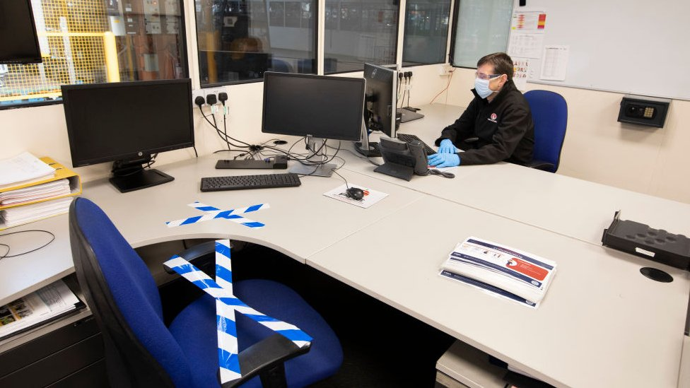 A man in an office wearing PPE