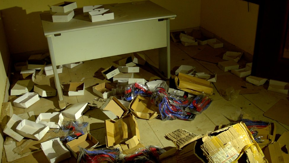 Boxes and electronic equipment are strewn on the floor of an office