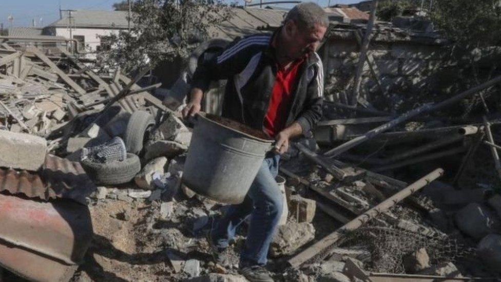 Seorang warga membersihkan puing-puing di ibu kota Nagorno-Karabakh, Stepanakert.
