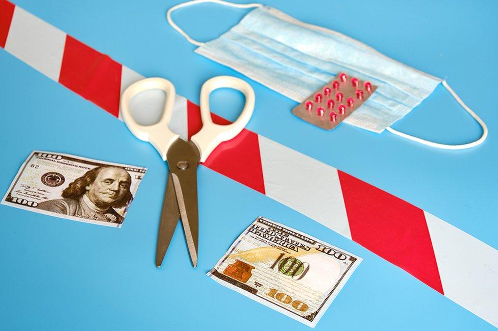 Tijeras y un billete de US$100 cortado