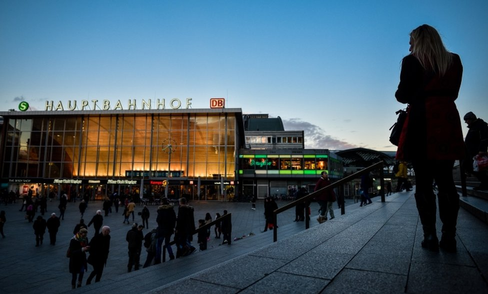 Women, seen in silhouette, stand near Hauptbahnhof main railway station, in Cologne, Germany