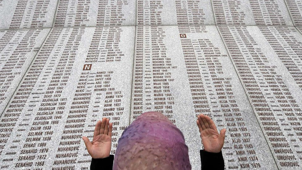 A Muslim woman prays near the list of victims of the Srebrenica massacre