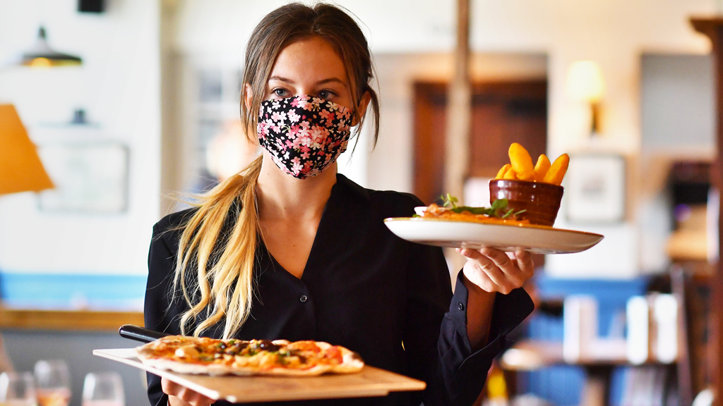 Waitress in pub wearing a face mask