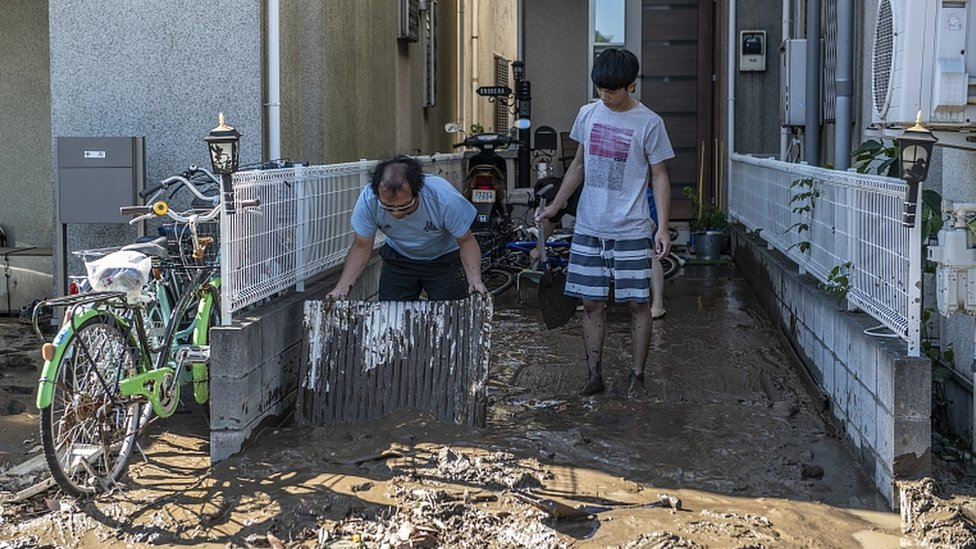 People clear mud from their homes after being flooded during Typhoon Hagibis, on October 13, 2019 in Kawasaki, Japan