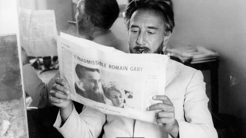 Romain Gary leyendo un periódico.