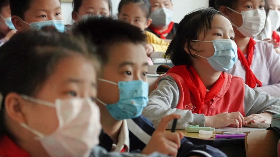 Grupo de niños con mascarilla en clase