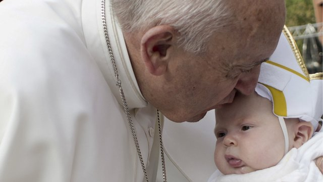 Pope Francis kisses a baby dressed as the Pope in Philadelphia