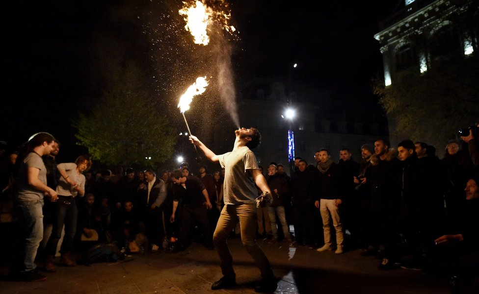 A fire eater performs during the 'Nuit Debout' gathering on 17 April in Paris