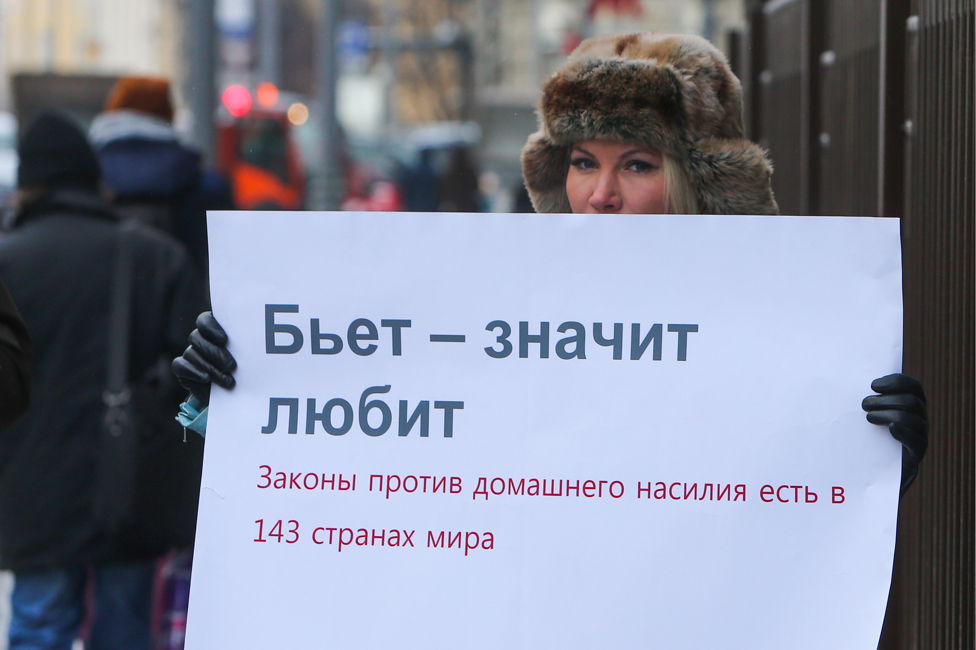 "A demonstrator pickets the Russian parliament quoting the saying, ""If he beats you it means he loves you"" - underneath the placard points out that 143 countries have a law on domestic violence"