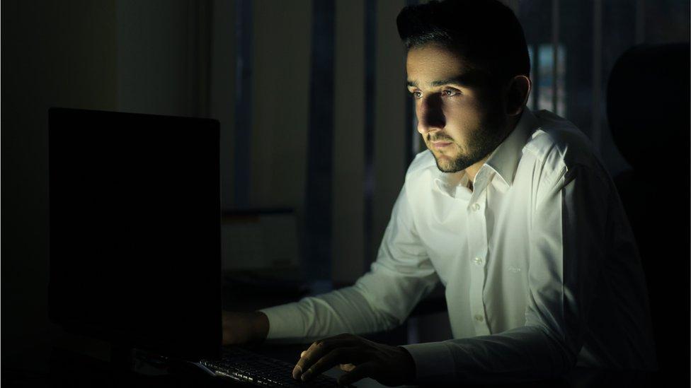 Un hombre a oscuras mira una pantalla.