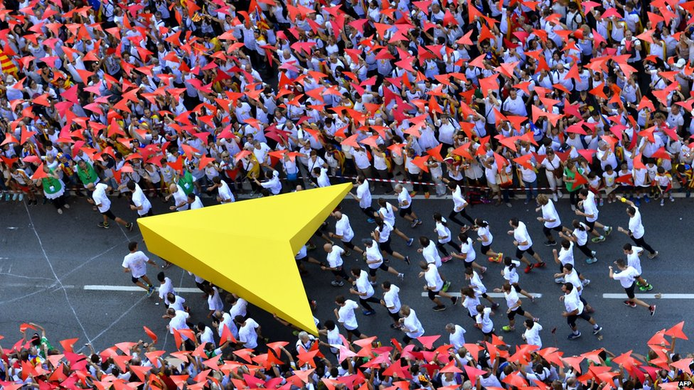 """Demonstrators hold a giant yellow cursor as they gather on Meridiana street as they wave """"Estelada"""" flags (pro-independence Catalan flags)"""