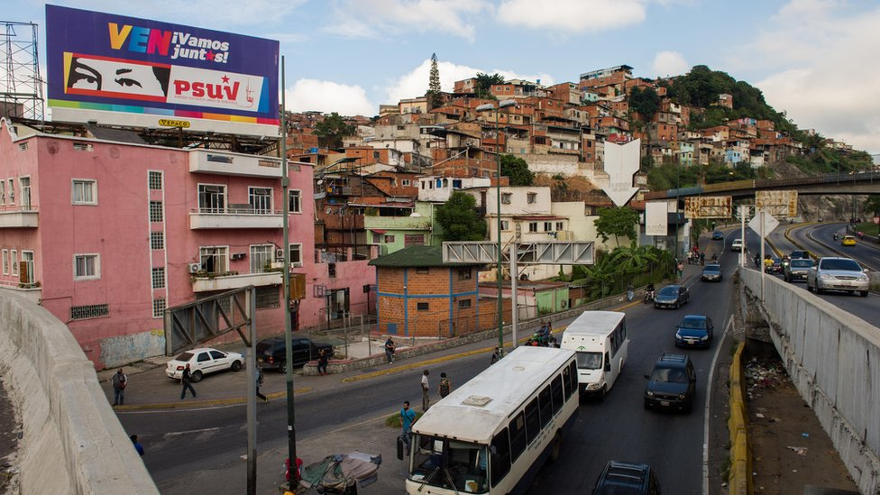 Billboard showing political slogans and depicting the eyes of late Venezuelan President Hugo Chavez, in Caracas