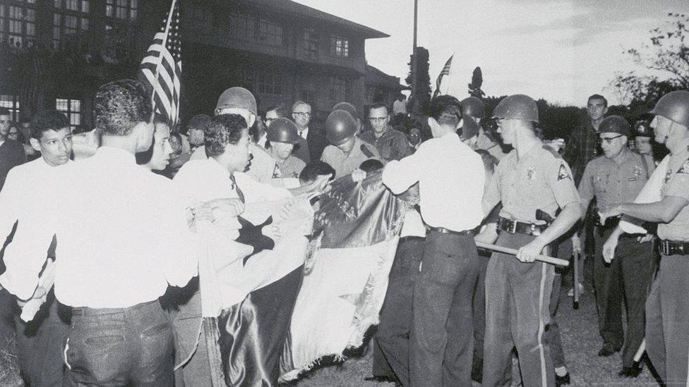 Estudiantes panameños frente a la policía zoneíta y rodeados de estadounidenses justo antes de que comenzaran los forcejeos para evitar que izaran su bandera.