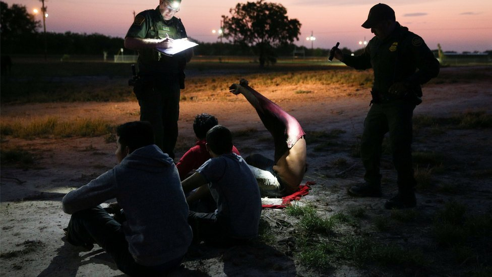 Border patrol agents apprehend immigrants who illegally crossed the border from Mexico into the US on 2 April