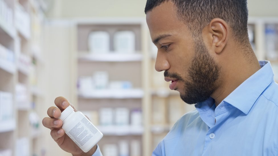 A man looking at a pill bottle in a pharmacy
