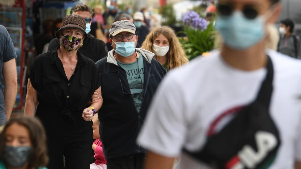 Personas caminando en la calle con mascarilla