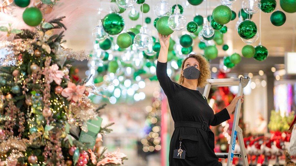 Shop worker hangs Christmas decorations