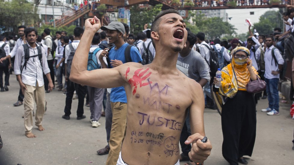 A Bangladeshi student shout slogans while blocking a road with others during a rally demanding safe roads on the seventh consecutive day of protests