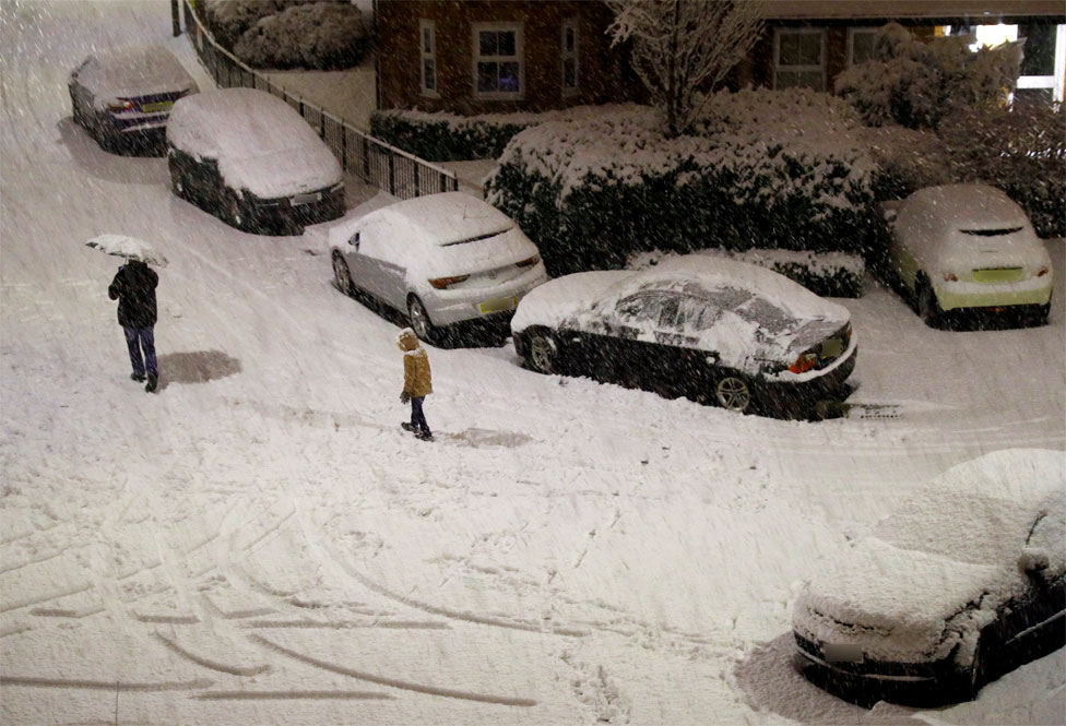 People walk along a snow covered road in Altrincham