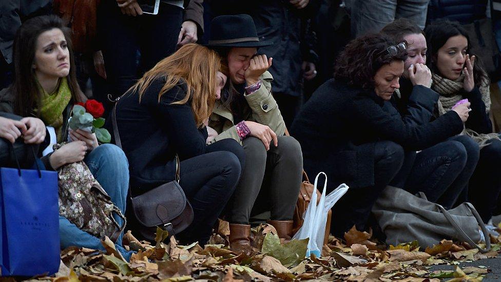 Gente reunida en París llorando a las víctimas.