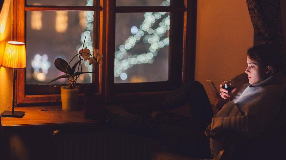 Žena pije pored prozora