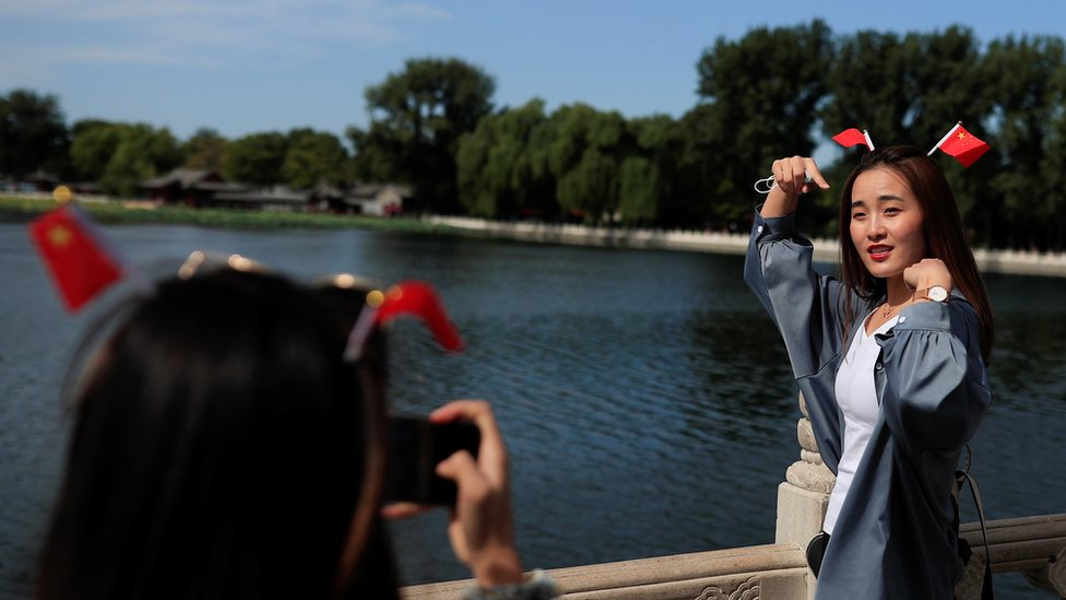 A woman poses for a photo in the tourist area surrounding Houhai Lake during Chinese National Day holidays in Beijing, China, October 2, 2020