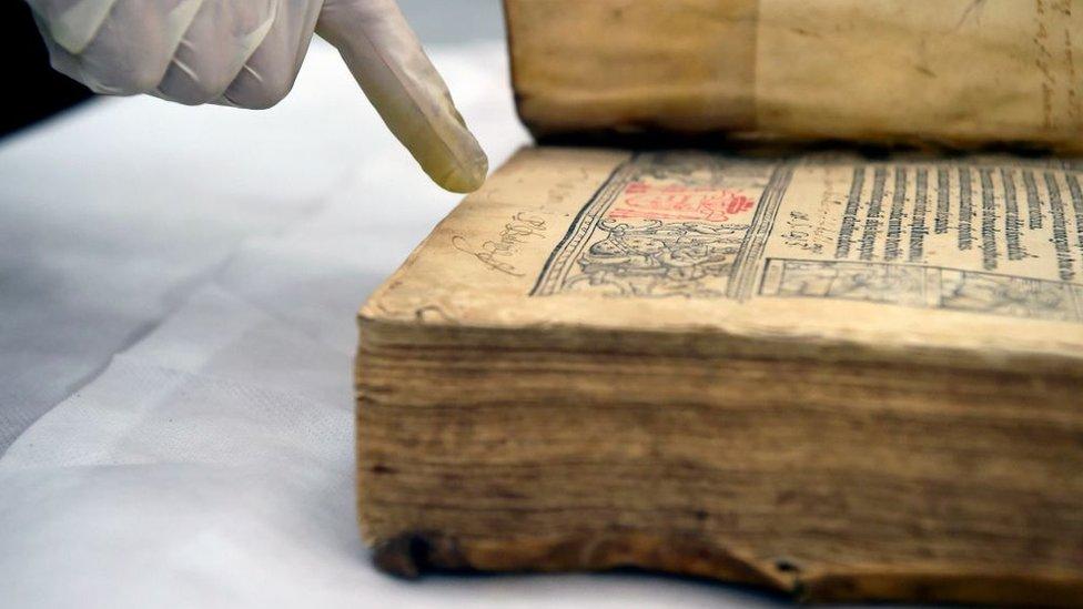 Libro antiguo y una mano con guante.
