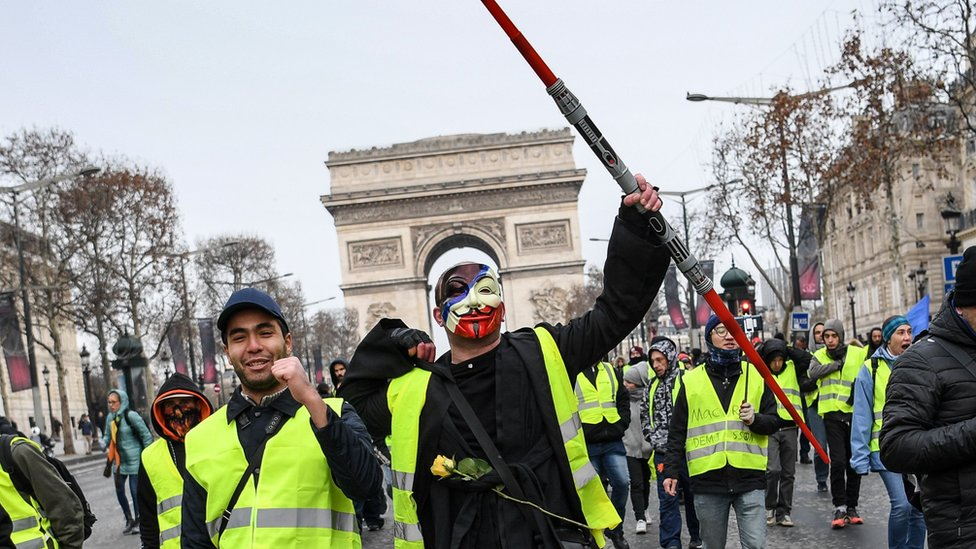 A man wearing an Anonymous mask and a yellow vest and holding a Star Wars Jedi light laser takes part in a demonstration to protest against rising costs of living they blame on high taxes, by the Arc de Triomphe in Paris, on December 15, 2018