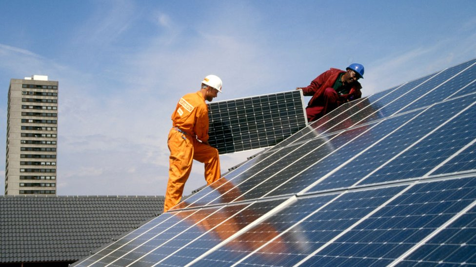 Engineers fitting solar panels to a roof at Silvertown Solar Village, Docklands, London UK