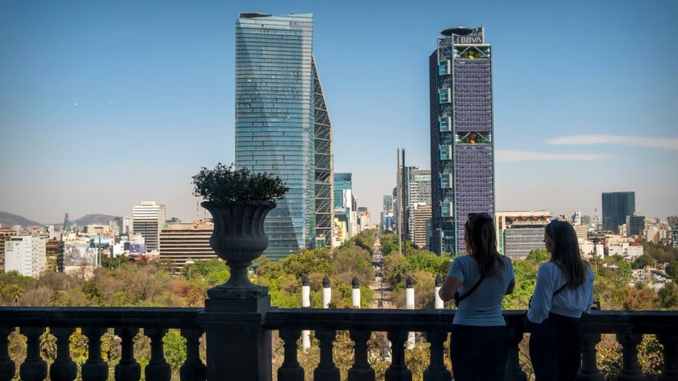 Dos mujeres de espalda mirando hacia el Castillo de Chapultepec y el Paseo de la Reforma en la distancia, Ciudad de México, México.