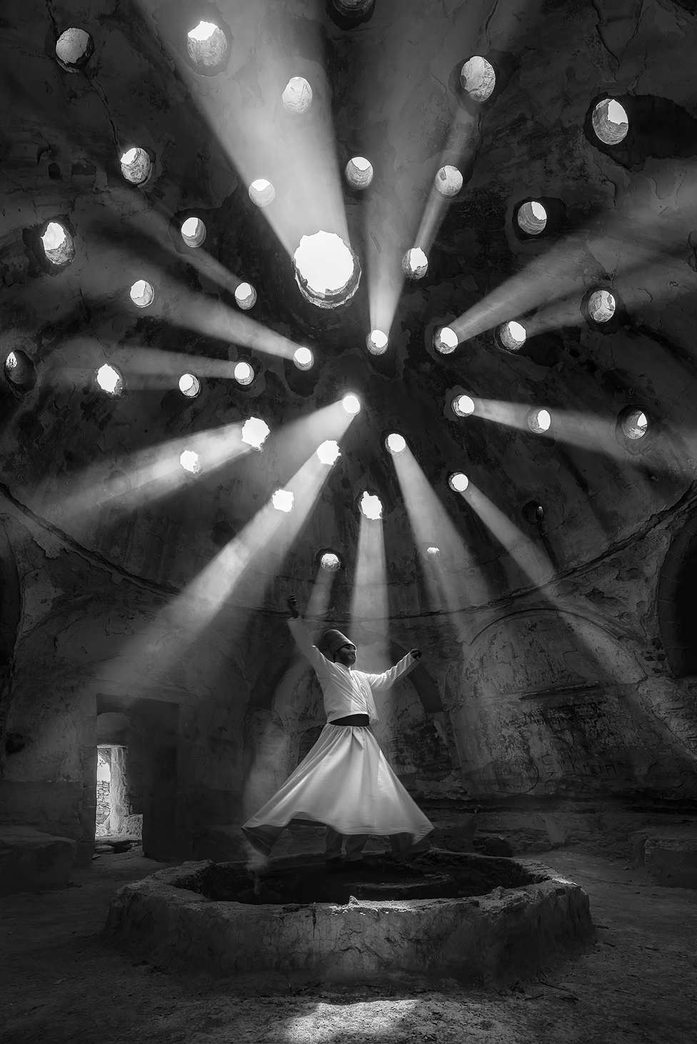 A whirling dervish raises his arms