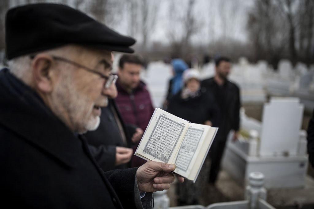 رجل من إغدير بتركيا يتلو آيات قرآنية أثناء زيارة قبور أقربائهم