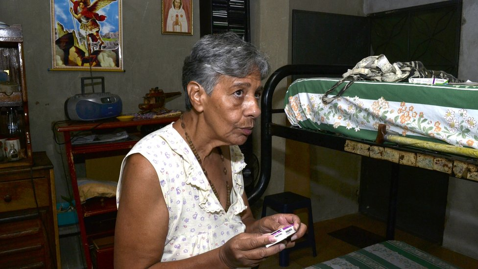 Norma Mújica holds a box of pills