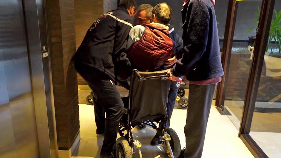 Alain es transferido de su silla de ruedas a una camilla
