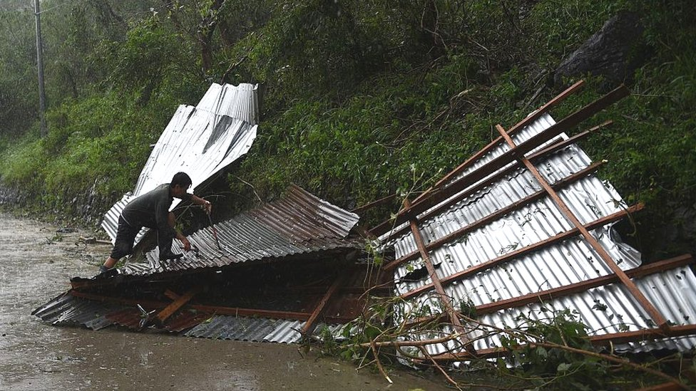 A resident tries to salvage his destroyed roof blown away at the heigh of typhoon Haima in Carranglan town on October 20, 2016.