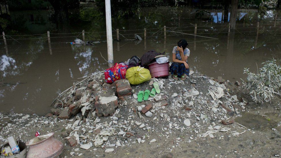 Woman sits on flooded ground in Kalay, Sagaing, Myanmar (3 Aug 2015)