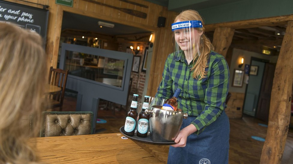 A woman serving beers in a visor