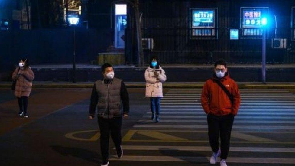 Çin'de maskeleriyle yürüyen insanlar